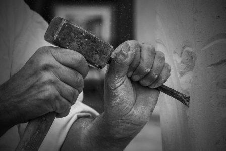 tailleur de pierre avec un burin et marteau